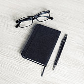 Black notebook, glasses, pencil