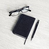 Black notebook, glasses, pencil