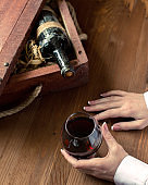 Human hand with a cup of red wine. Old bottle in vintage crate among wood shaving on wooden background, selected focus