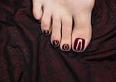 Female toes with beautiful bloody red glossy pedicure on the drape of dark shiny fabric, close up. Bare foot.