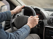 Male hands on steering wheel, inside cab, close up. Man driving a car.