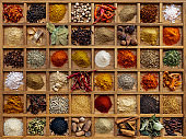 Variety of colorful, organic, dried, vibrant Indian food spices in a wooden compartment box.