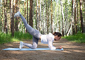 Fit caucasian girl in white sportswear does one leg kicks exercise. Workout outdoor in the park, in summer, selective focus.