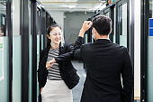 Young asian business colleague wearing face shield, face mask and elbow bump greeting on corridor in office
