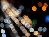 Abstract bokeh night light background, blurred lights traces from cars on road, de focused city traffic on street at night