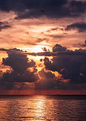 Sunset over tropical sea with colorful sky in cloudy and airplane