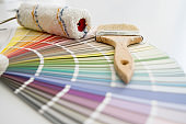 Paint Brush And Roller With Color Chart Are On Table