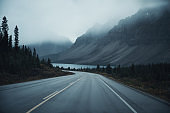 Mysterious road trip with rocky mountains in misty on gloomy at Banff national park