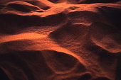 Rippled glowing sand of desert at sunset