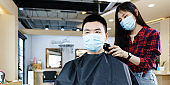 Happy Asian man wearing a mask use haircut service in Barber shop. Woman hairdresser provide service mind. Hairdressing equipment is clean. End of quarantine and return to open salon hair work
