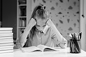 The schoolgirl in a bad mood rests her head on her hands and looks at the textbook.