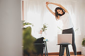 Asian woman doing stretching along with online class from laptop at home