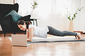 woman doing plank exercise at home while watching online workout session from laptop