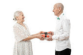 Cheerful elderly couple in white closes looking at each other and exchanging gifts isolated on white background, celebrating valentine's day
