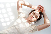 attractive woman in beatiful white dress lying on the light floor with closed eyes and circle sunlights fall on her