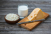 Cottage cheese, a piece of cheese on a cutting board and a glass of milk on an old wooden table. Rustic vintage style, dairy products.