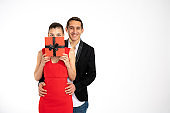 Copyspace photo of two people together loving each other presenting you gift, brunette female in red dress covered her face with red gift box, his boyfriend hugging her and loooking at the camera isolated over white color background