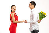 Photo of charming cute nice pretty sweet trendy white couple of two people together with him gifting his wife yellow tulips flowers and her rejoicing with getting flowers and looking at the camera isolated over white background