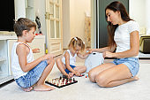 Cheerful mom is playing with her kids sitting on the white carpet in the living room