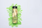 Health care, fitness, healthy nutrition diet concept. Fresh cool lemon cucumber mint infused water, cocktail, detox drink, lemonade in a glass jar with paper leaves. Light top view flat lay background