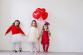Kids with red balloons for birthday in the interior
