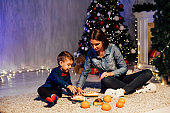 mom and young boy open Christmas presents Christmas tree new year holiday