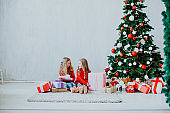 Christmas holiday two girl with presents new year Christmas tree on a grey background gifts