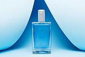 men's perfume in beautiful glass bottle on blue background