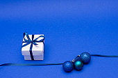 white surprise gift box with ribbon and christmas decorations on blue background, copy space