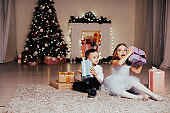 boy and girl family opens Christmas gift new year holiday lights Christmas tree garlands