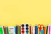 Colorful stationery for kids on yellow background with a copy space