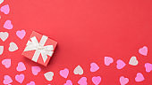 holiday gift box with ribbon and hearts on red background. Copy space for text. Template for Valentine's Day. Banner