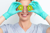 Beautician holding kiwi pieces over eyes.