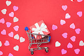 Shopping cart with gift box and hearts for Valentine's Day on red background