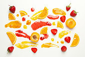 Apricot, strawberry, orange and jams on white background
