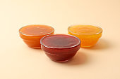 Bowls with jam on beige background, space for text