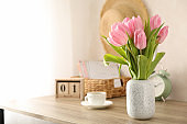 Composition with tulips in vase on wooden background, space for text