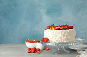 Composition with delicious berry cream cake on gray table. Tasty dessert