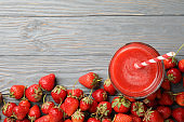 Tasty strawberry and cocktail on wooden background, top view. Summer berry