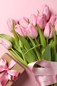 Bouquet of tulips and gift box on pink background, top view