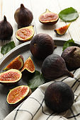 Tray with fig, leaves and towel on wooden background