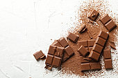 Tasty chocolate and powder on white background. Sweet food