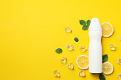 Spraying deodorant, ice and lemon on yellow background, blank space for text