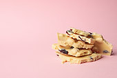 White chocolate pieces on pink background. Sweet food