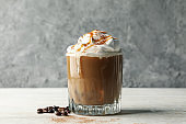 Glass of ice coffee with poured cream on wooden table