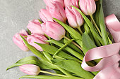 Tulips with ribbon on grey background, top view