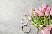 Eight made of ribbon and tulips on grey background, space for text