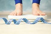 Woman stands on the scales. Measuring tape. Weight loss