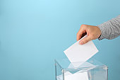 Man putting ballot into voting box on blue background