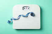 Scales and measuring tape on mint background. Weight loss concept
